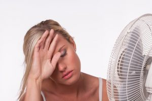 woman-in-front-of-fan-hand-on-head